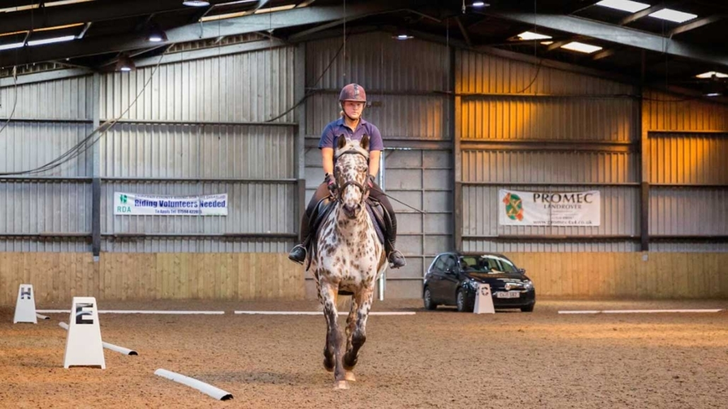 Student riding a horse in the indoor arena Pencoed Campus